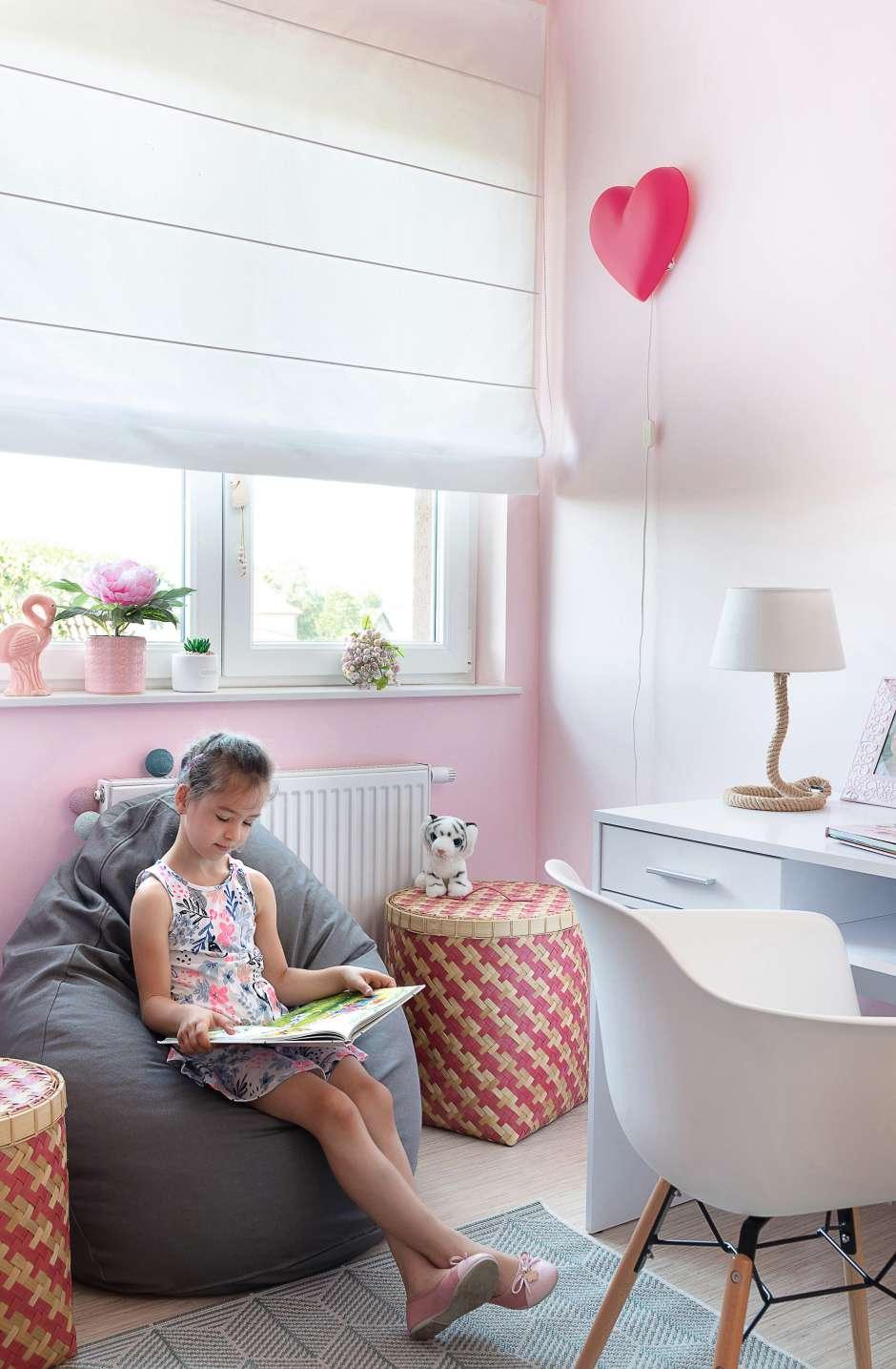 Девочка читает книгу в своей маленькой комнате